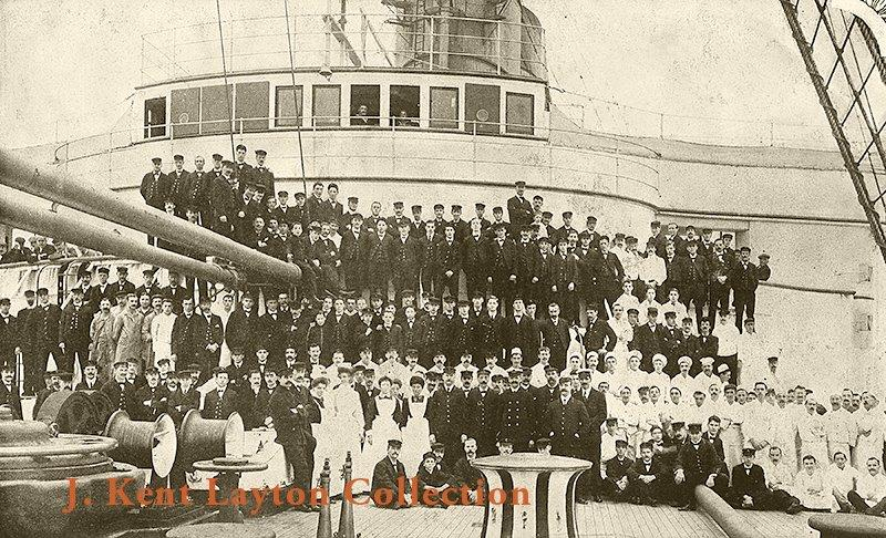 The crew of the Lusitania was like a big family. Here members pose in front of her Bridge on the Forecastle, apparently after she had just suffered damage in a storm--note the covered windows of her Bridge. © J Kent Layton Collection