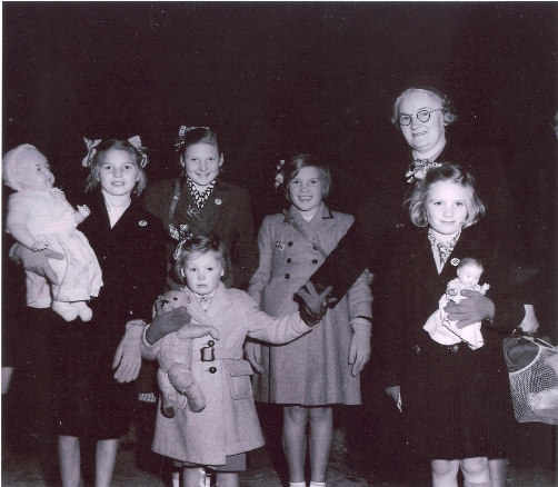 Black and white image of school children clutching dolls