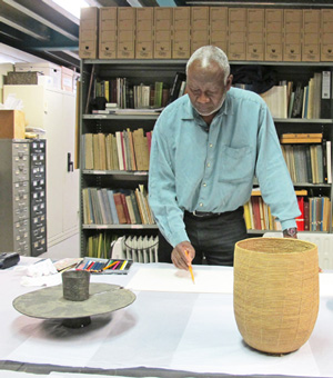 Atta Kwami sketching African artefacts in the museum store