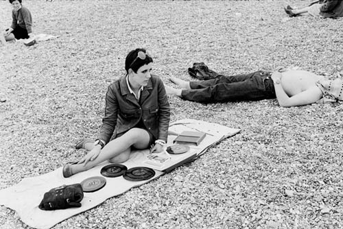 Girl sitting on the beach playing records