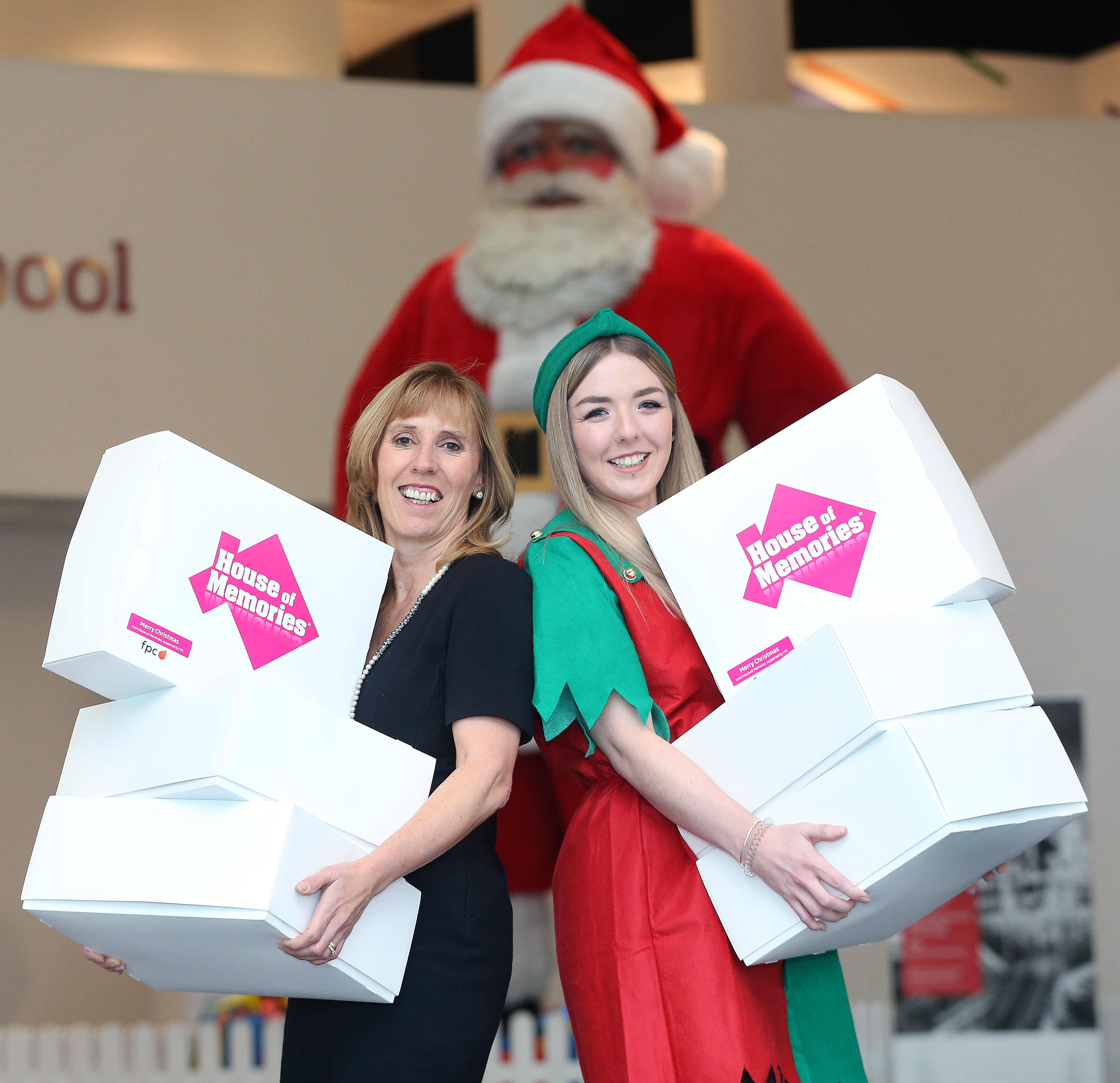 Blackler's giant Santa at the Museum of Liverpool overlooks two of Santa's elves carrying House of Memories Christmas-themed memory boxes