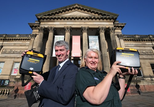 Two people holding defibrillators standing outside the Walker Art Gallery