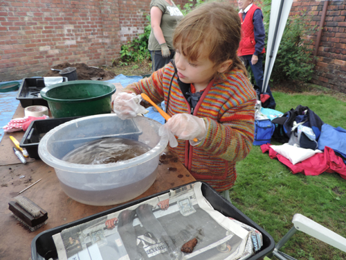 Young archaeologist washes finds on site in Rainford