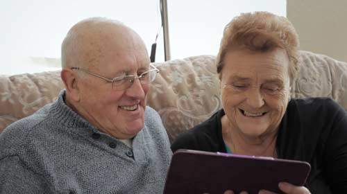 A smiling gentleman and lady looking at a tablet