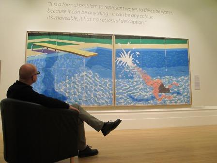 Image of man sitting in front of David Hockney painting