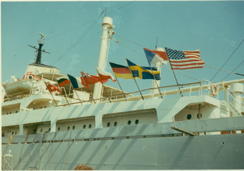 Flags of different nations flying on the side of a ship