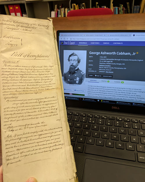 document next to computer screen showing info on George Ashworth Cobham Jr
