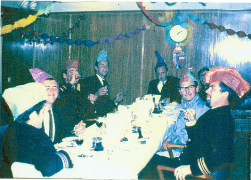 Group of men sat round a dining table on board ship with party hats and decorations.ith