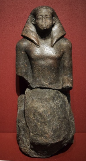Frontal image of a statue showing a seated man