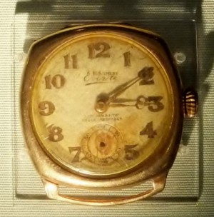 Gold coloured wrist watch missing its strap. Hands stopped at ten past three.