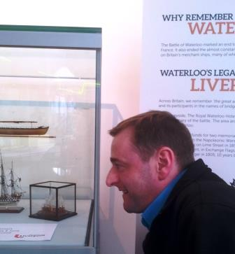 Mike Butchard, Visitor Assistant, inspects one of the miniature ship models.