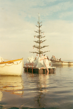 Large Wooden Christmas Tree floating beside two small boats.