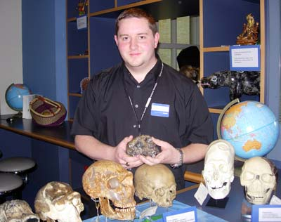 a smiling man in a blue shirt surrounded skulls