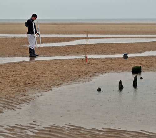 Someone using technical equipment to survey a partly-exposed shipwreck on a beach
