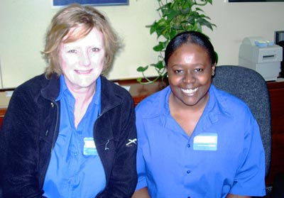 Photo of two smiling women in blue shirts and staff badges