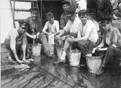 Black and white photo of men washing fabric in buckets on deck of a ship