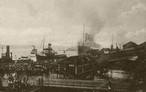 crowds of people on the landing stage in front of a large ship