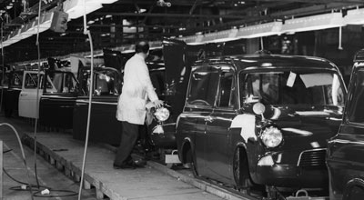 man standing by row of vans on a factory production line