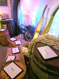 Gallery shot showing barrels with signs reading corn, salt and sugar.