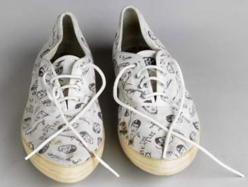a creamy coloured pair of pointed sneakers with Beatles signature design