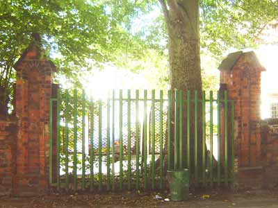 photo of old, red brick gate posts with a modern green fence between them