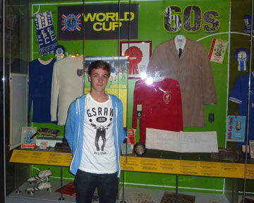 Ben Forshaw stood next to a display cas with football objects at the Museum of Liverpool