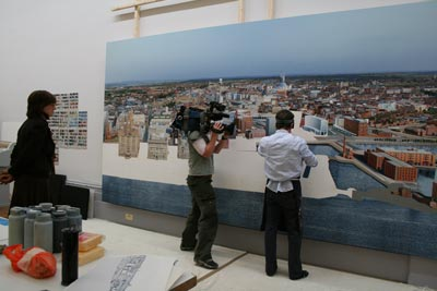Man being filmed painting a large picture