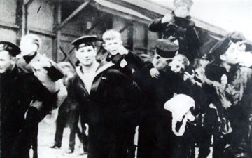 Black and white photo of boys being carried by sailors