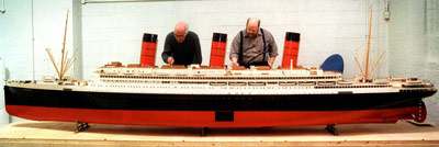 a large red and black ship model being worked on ny two men