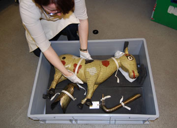 woman getting a large model horse out of a box