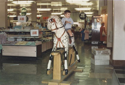 young boy riding rocking horse in Blacklers department store
