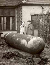 Black and white photo of a man and woman outside their house standing next to a large bomb
