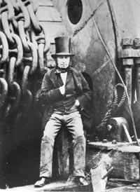 Black and white photo of a man in a top hat and waistcoat leaning against a huge wheel of chains
