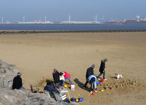 recent photo of people on a beach in winter clothing making sand castles