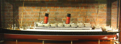 large ship model of a liner with two red funnels, lots of life boats and masts