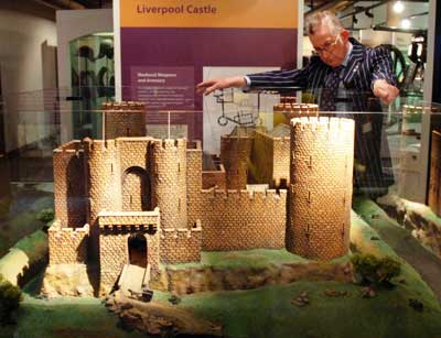 Photo of a man looking at a model of a castle within a glass case