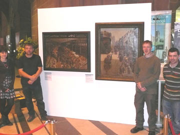 Museum staff stood with the paintings on display at Liverpool Cathedral
