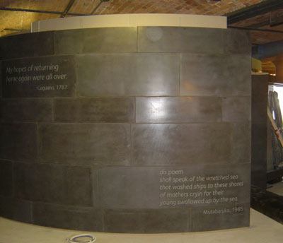 a shiny curved grey wall with writing on it
