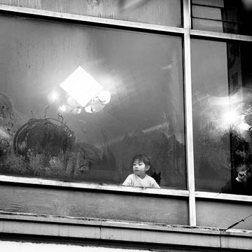 Black and white photograph of young girl looking out from an upstairs window
