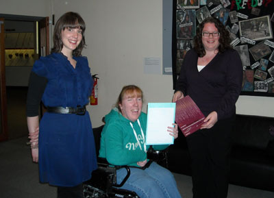 three smiling women, one holding up a certificate