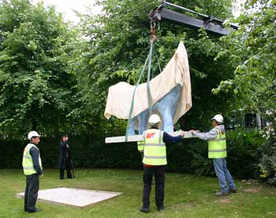 Photo showing a large lamb-shaped sculpture being whinched into place on a lawn by a large crane. People in hard hats are supervising.