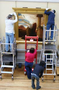 People on scaffolding and ladders hang a large painting
