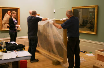 Team of people unwrap a large painting