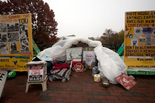 tent surrounded by protest signs and banners