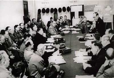 Black and white photo of men in uniform sitting around a board table.