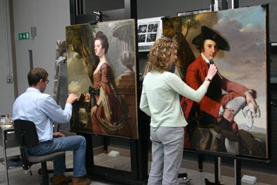 conservators working on 2 paintings