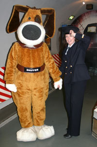 Roleplayers dressed as a customs officer and sniffer dog