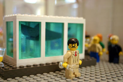 A suited lego man stands before a lego shark in a lego fishtank