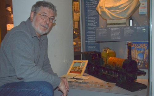 man next to train model in museum display