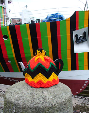 colourful tea cosy in front of a ship painted with a similar pattern